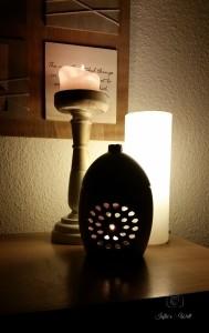 eine Votivkerze zusammen mit einem Duftlicht und einer kleinen Lampe sorgen für gemütliche Stimmung im Wohnzimmer